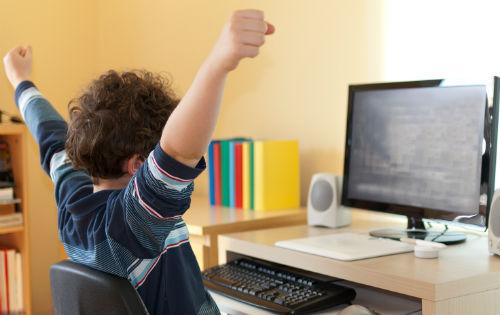 Criança brincando com jogos digitais educativos na escola.